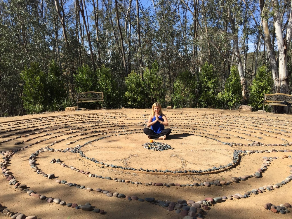 Heidi doing a yoga pose in the middle of a rock circle with sand.