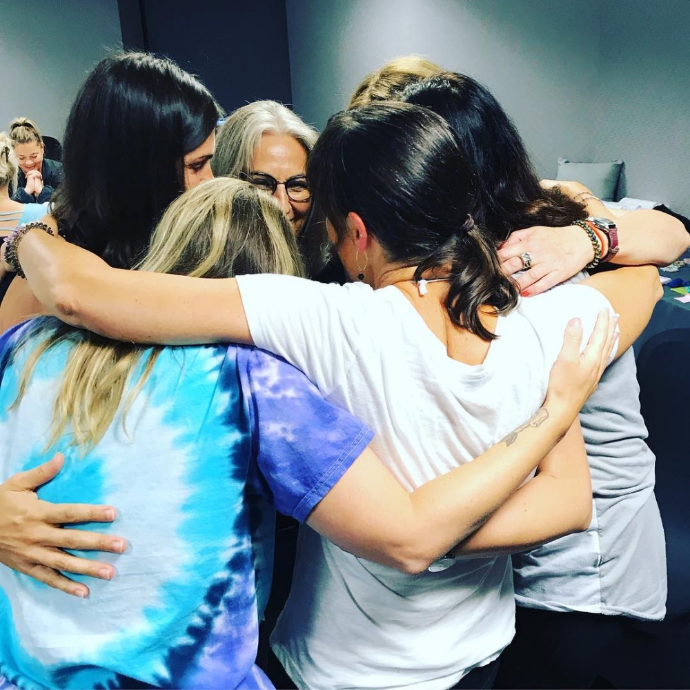 Women with their arms wrapped around each other, huddled in a close circle.