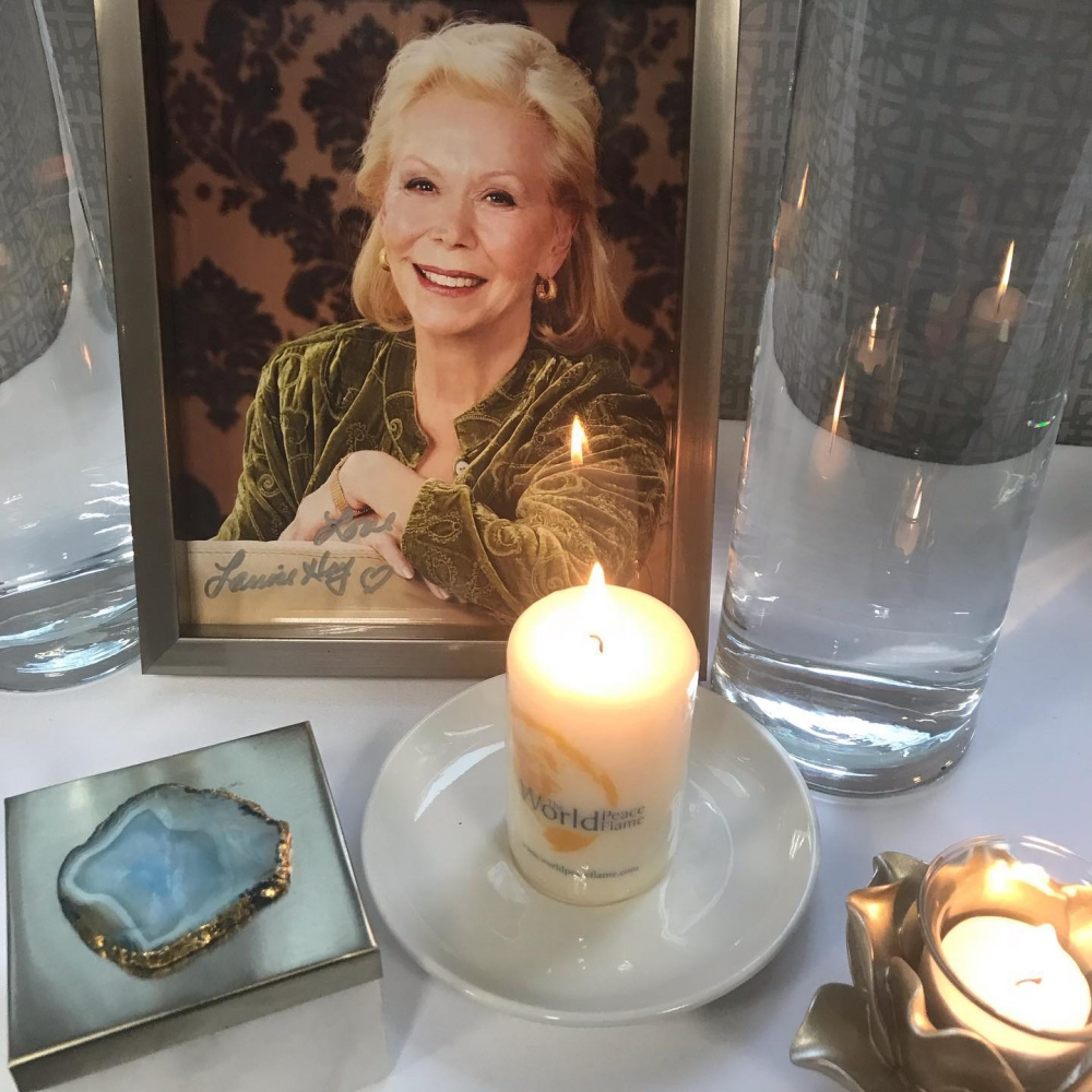 Framed picture of Louise Hay on a table with a candle.