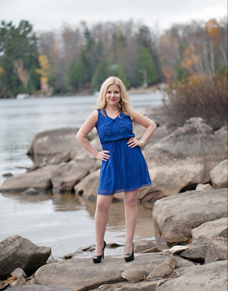 Heidi standing on rocks along the lake in a blue dress and high heels.