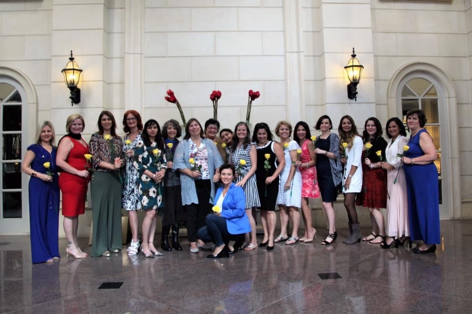 Group of women holding yellow roses who have completed Heal Your Life Training.