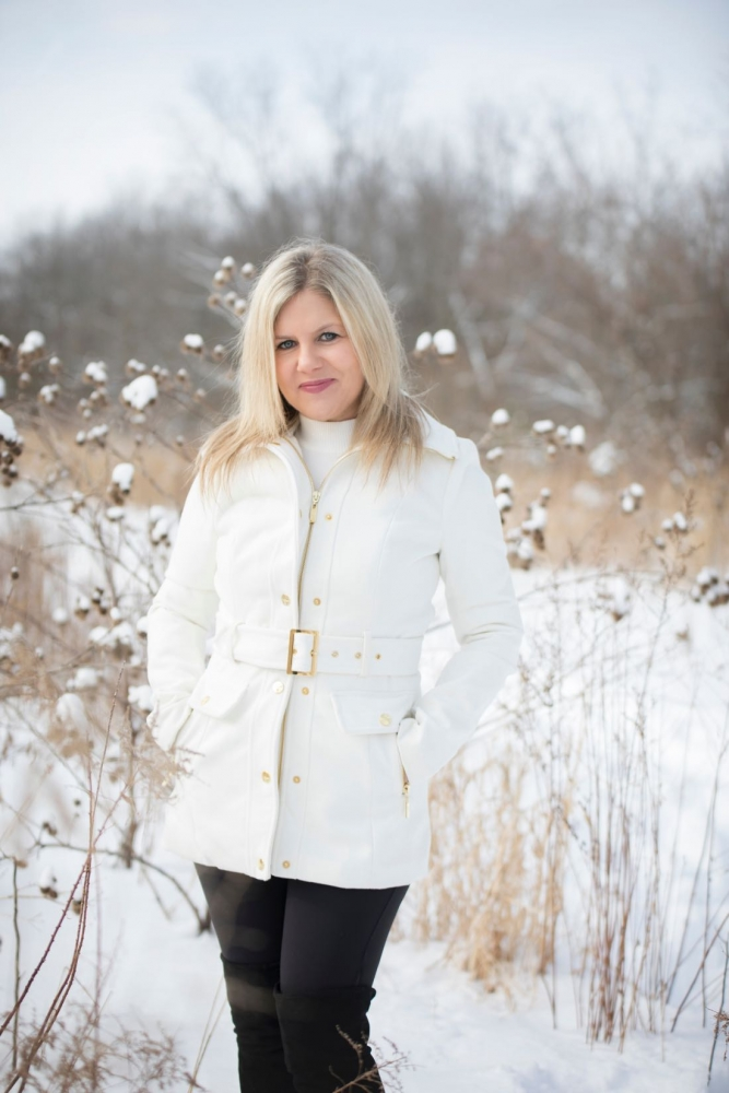 Heidi in a white jacket outside in the snow.