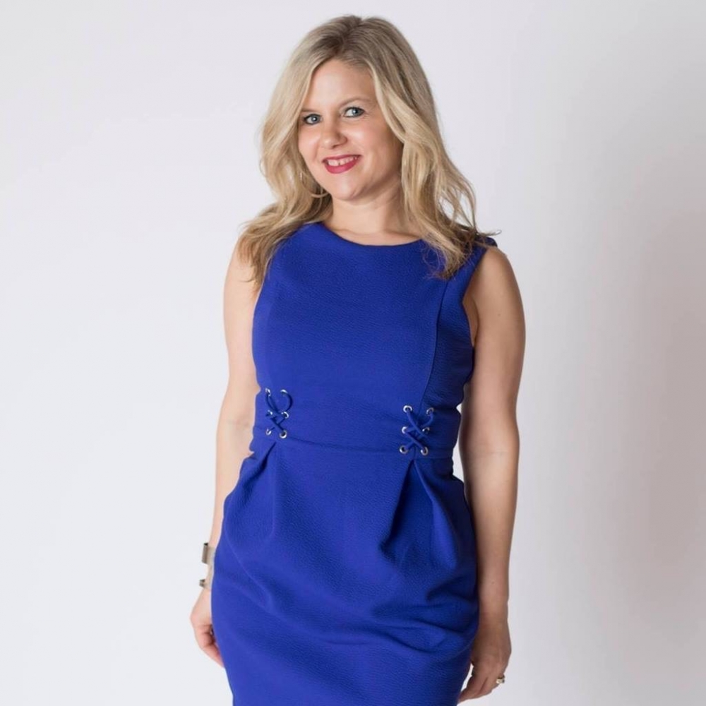 Heidi posing for the camera in a blue dress.