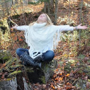 Heidi sitting in a forest during fall with her arms open and face to the sky.