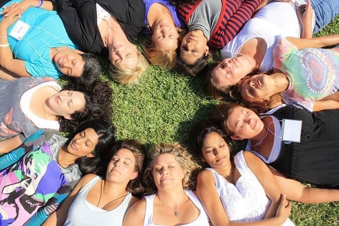 Women laying in a circle on the grass.
