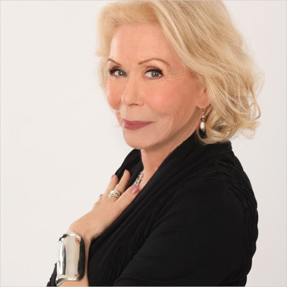 Louise Hay with her hand on her heart.