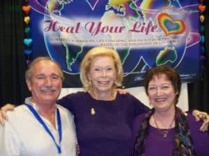 Louise Hay with her arms around other Heal Your Life Trainers.