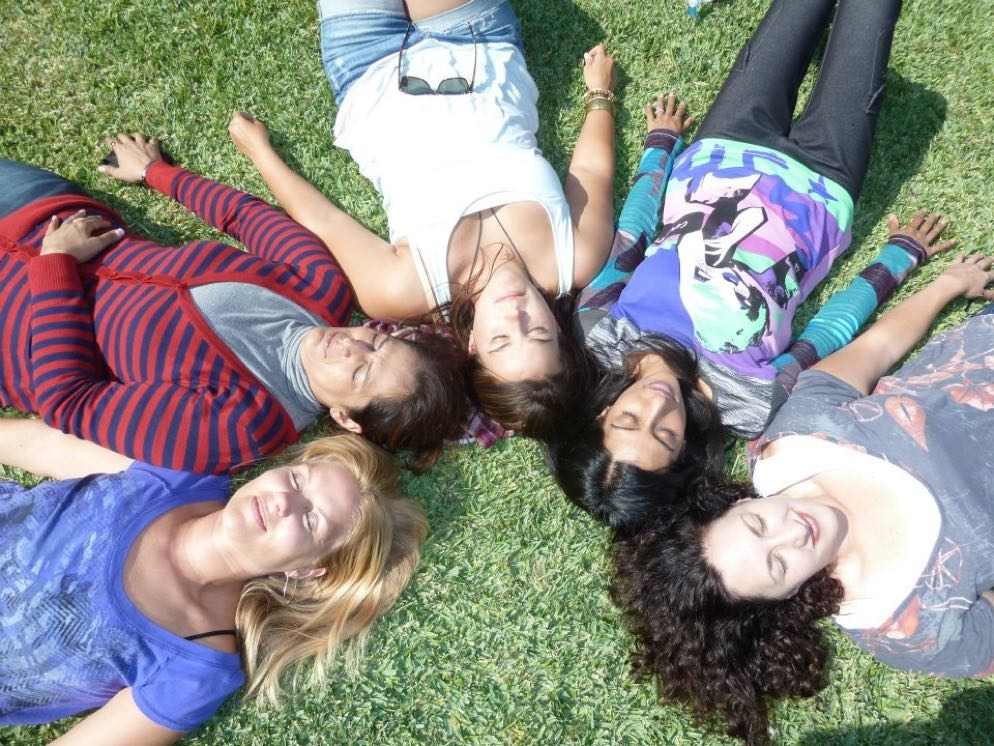 Women laying on the grass in a circle with their eyes closed.