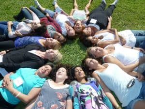Group of women in a circle laying on the grass with their eyes closed.