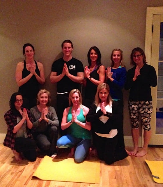 Group of people with their hands together after attending a yoga class with Heidi.