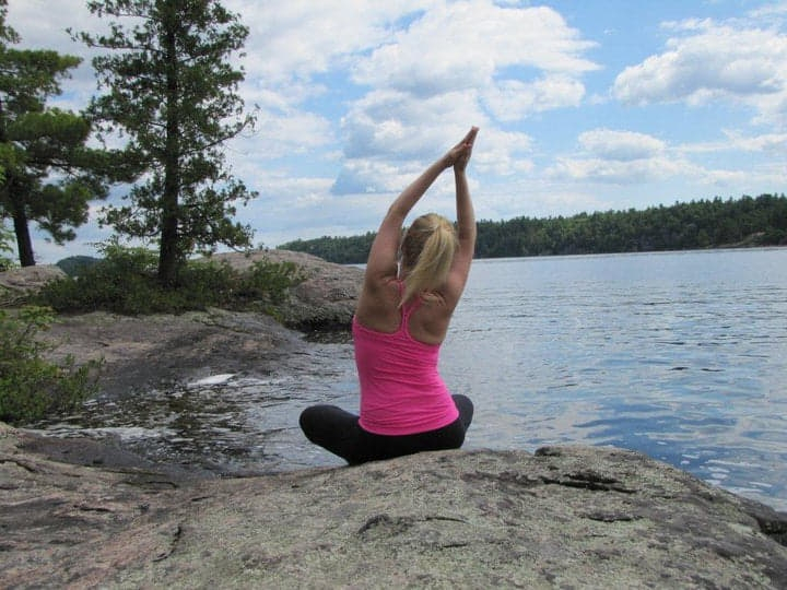 Heidi doing a yoga pose on a rock along the lake.
