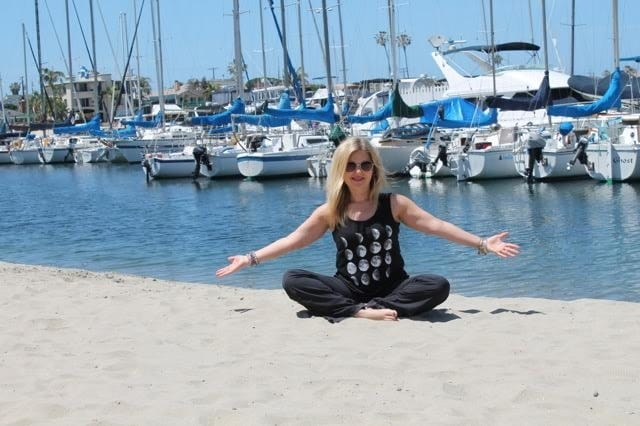Heidi sitting on the sand by the ocean with her arms stretched out.