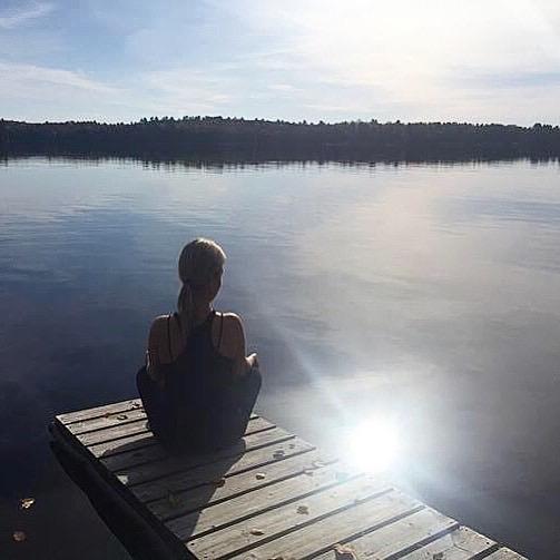 Heidi doing a yoga pose on a dock at the lake.