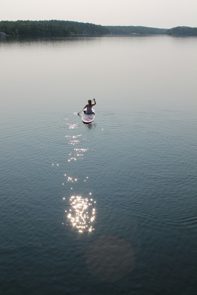 Heidi paddle boarding in the middle of the lake.