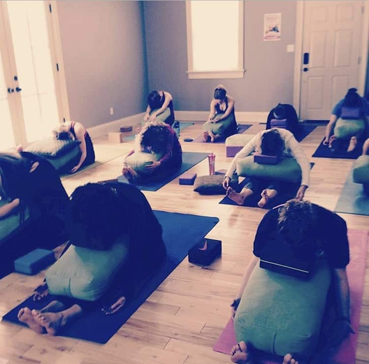 Group of people during a yoga class doing a pose.