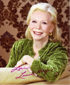 Louise Hay smiling at the camera in a green shirt.