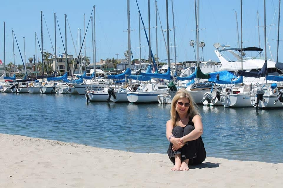 Heidi sitting on the sand by the ocean with boats in the background.