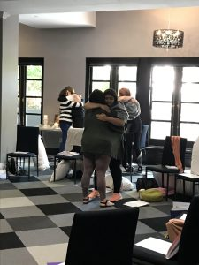 Groups of women hugging during the Heal Your Life Teacher Training.