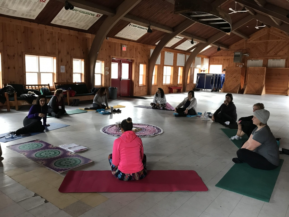 Several women sitting on yoga mats chatting during a workshop.