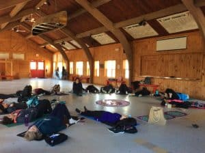 Women laying on yoga mats in a circle during a Heal Your Life workshop.