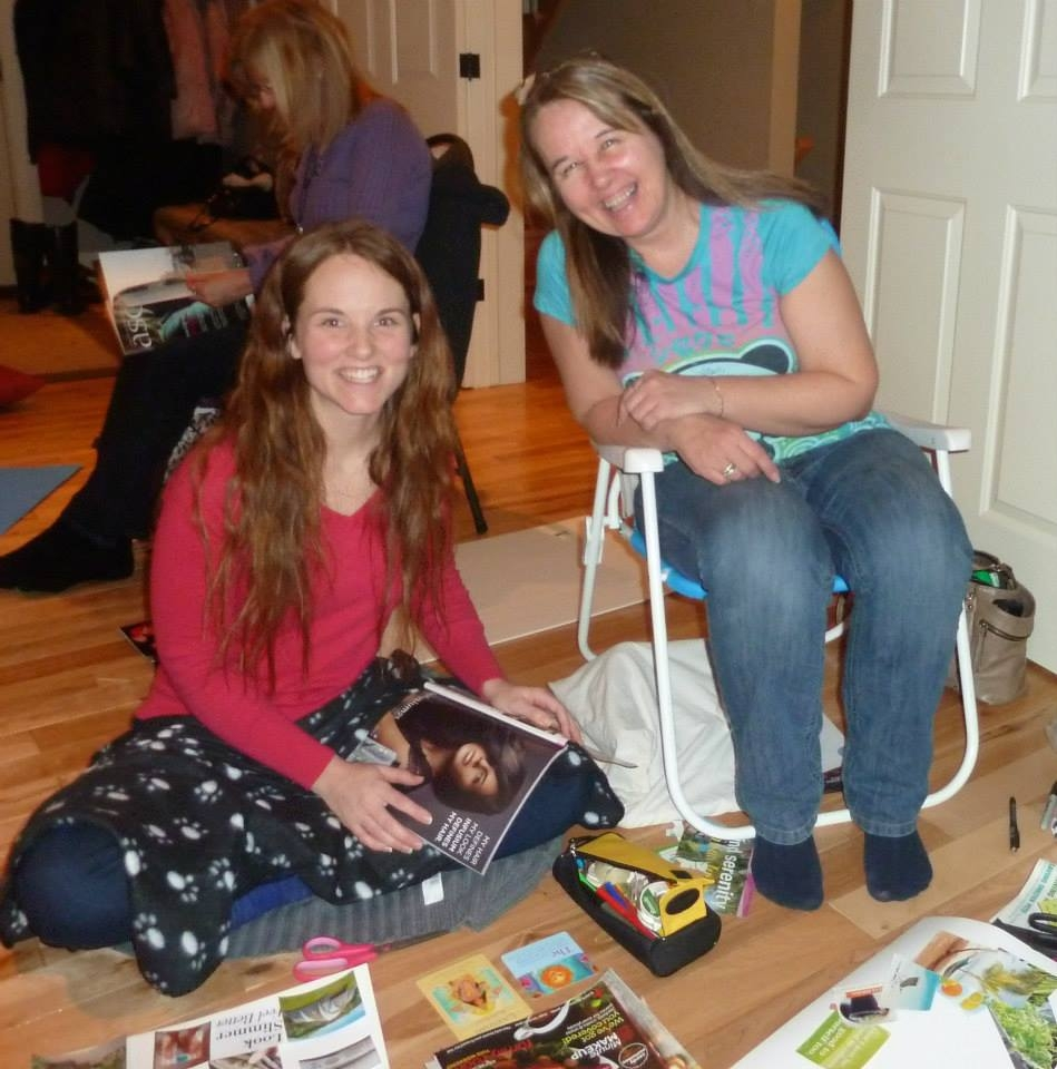 Two women sitting and cutting out images from a magazine.