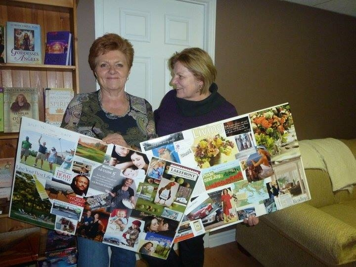 Two women holding their vision boards.