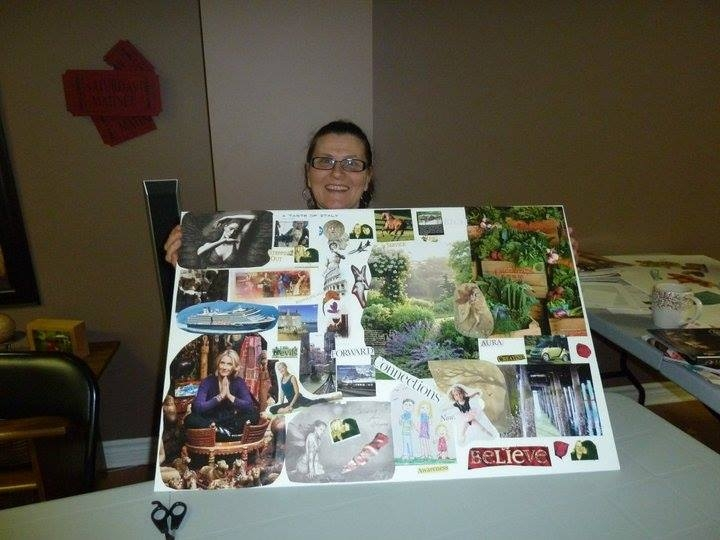 A woman holding a vision board during a workshop.